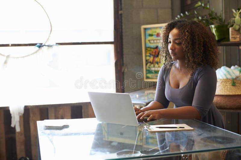 Gemengde rasvrouw die in laptop van het winkelgebruik aan de teller werken stock afbeelding