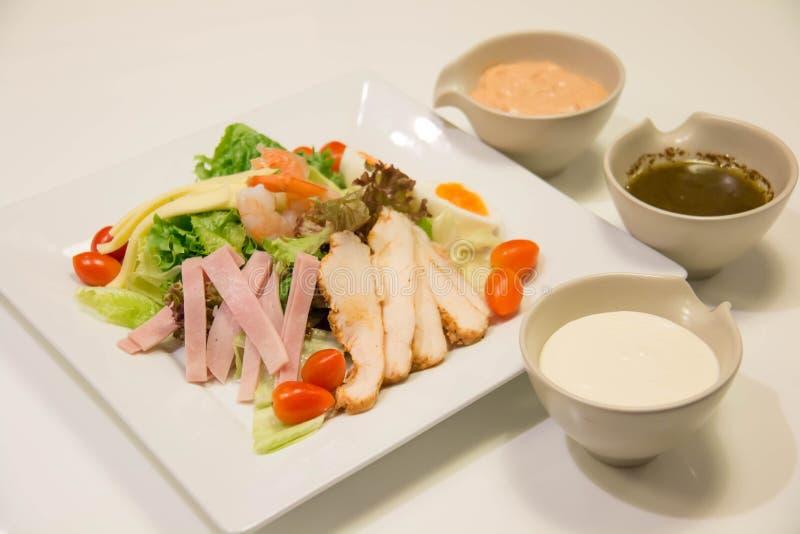 Gemengde salade met kip, ham, saus, en groente stock foto's
