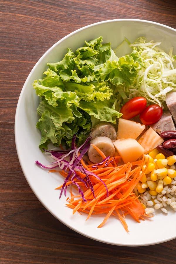 Gemengde salade met tomaten, graan, wortelen, kantaloep, rode bonen, stock foto