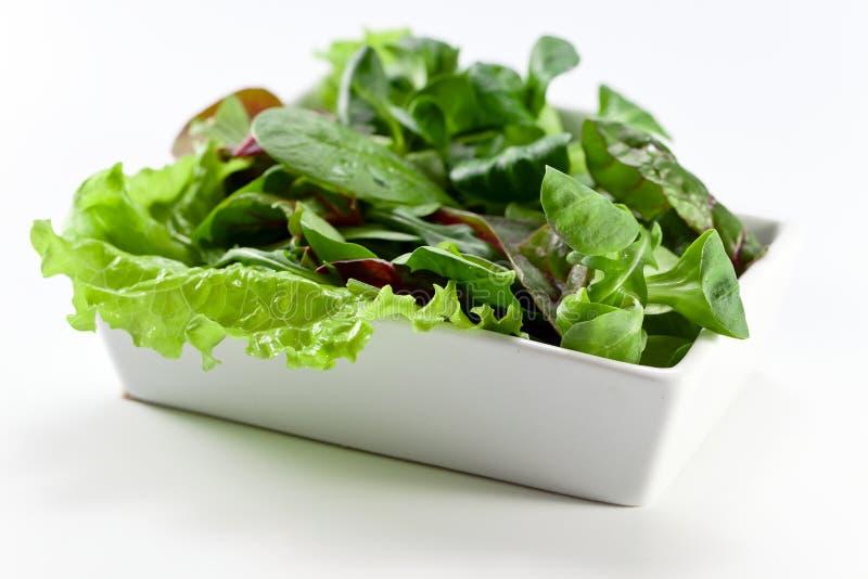 Gemengde salade op witte lijst stock afbeeldingen
