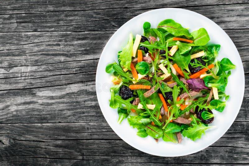 Gemengde sla, spinazie, wortel, ham, kaas en gedroogde pruimensalade, hoogste-mening stock foto's