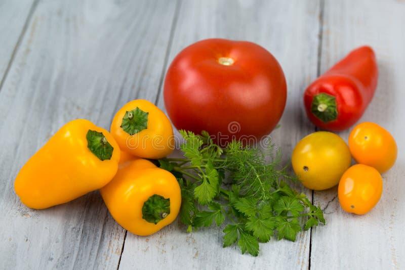Gemengde verse gekleurde groenten, kersentomaten, minipaprika, tomaat en verse kruiden op een houten achtergrond stock fotografie