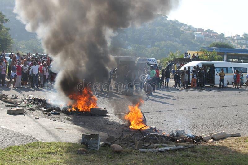 Gemenskap som arrangerar en protest som blockerar en väg under ett taxislag i Durban Sydafrika arkivfoton
