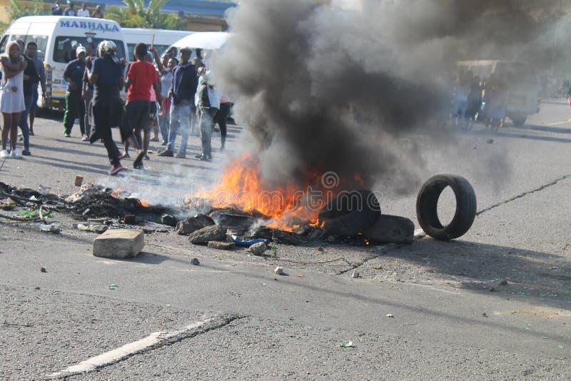 Gemenskap som arrangerar en protest som blockerar en väg under ett taxislag i Durban Sydafrika royaltyfri fotografi