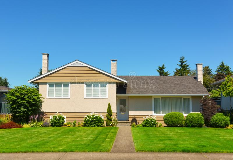 Gemiddeld familiehuis met groen gazon en bomen vooraan op blauwe hemelachtergrond stock fotografie