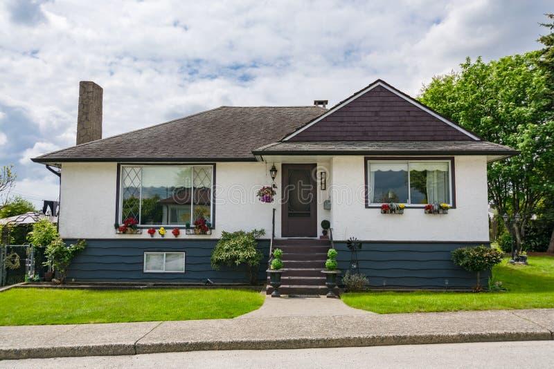 Gemiddeld familiehuis met groen gazon op bewolkte dag in Canada royalty-vrije stock afbeelding