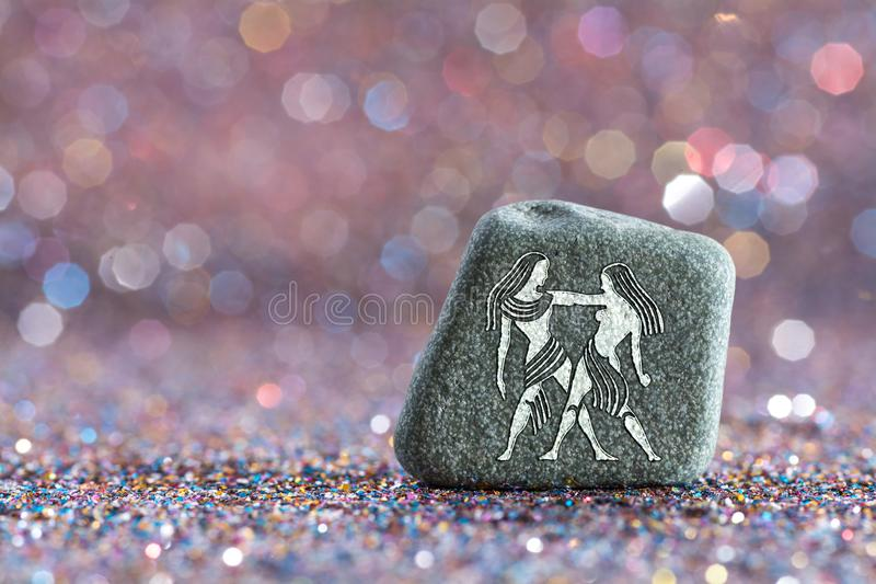 Gemini zodiac sign. A green stone with Gemini zodiac sign on glitter boke light background royalty free stock photo