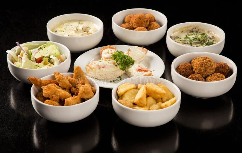 Gemischte brasilianische Snäcke, einschließlich Gebäck, gebratenes Huhn, Salat lizenzfreies stockfoto