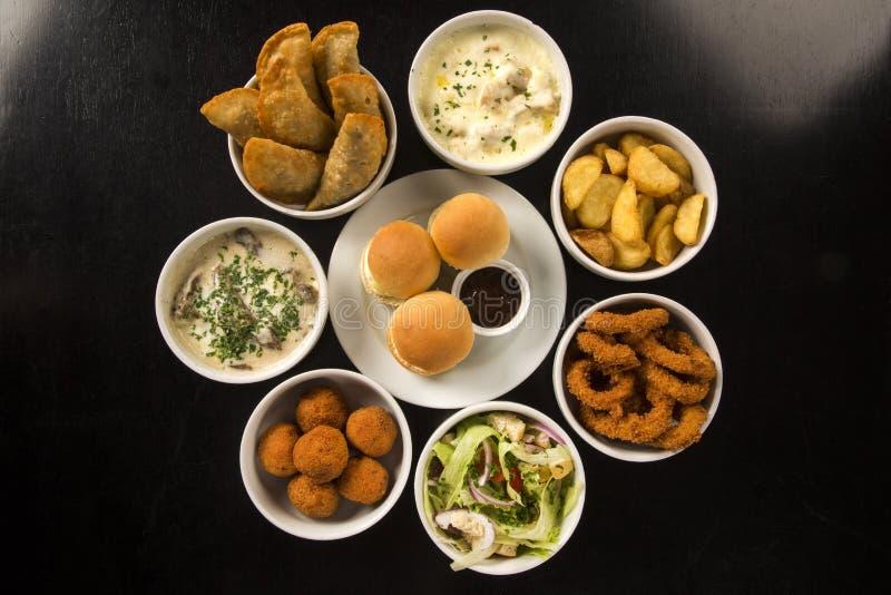Gemischte brasilianische Snäcke, einschließlich Gebäck, gebratenes Huhn, Salat stockbilder