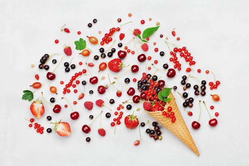 Gemischte bunte Beeren im Waffelkegel auf weißer Tischplatteansicht in Ebene legen Art lizenzfreie stockfotografie