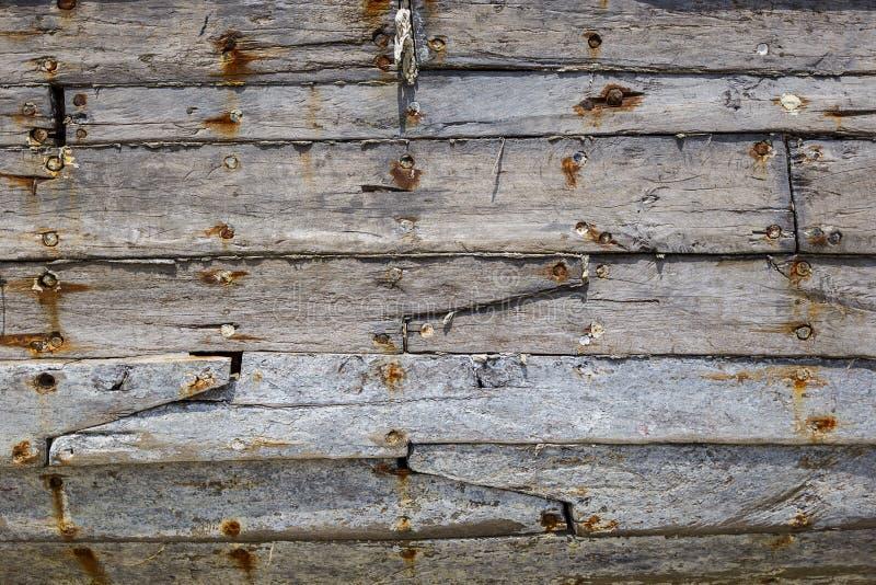 Gemischte hölzerne Beschaffenheiten von verwittertem rauem des Bootsrumpfs mit rostigen Nägeln und Sprüngen stockbild