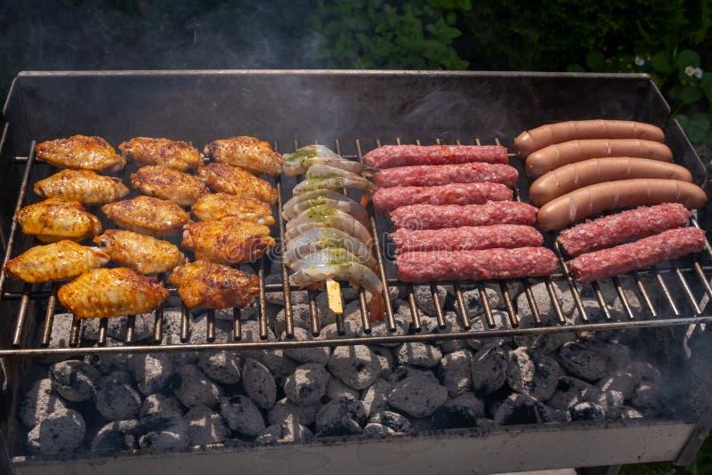 Gemischte Zusammenstellung des marinierten Fleisches, des Huhns und der Garnelen, die auf heißen Kohlen auf einem BBQ grillen lizenzfreie stockbilder