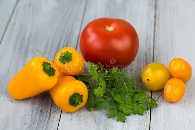 Gemischtes frisches farbiges Gemüse, Kirschtomaten, Minipaprika, Tomate und frische Kräuter auf einem hölzernen Hintergrund stockbilder