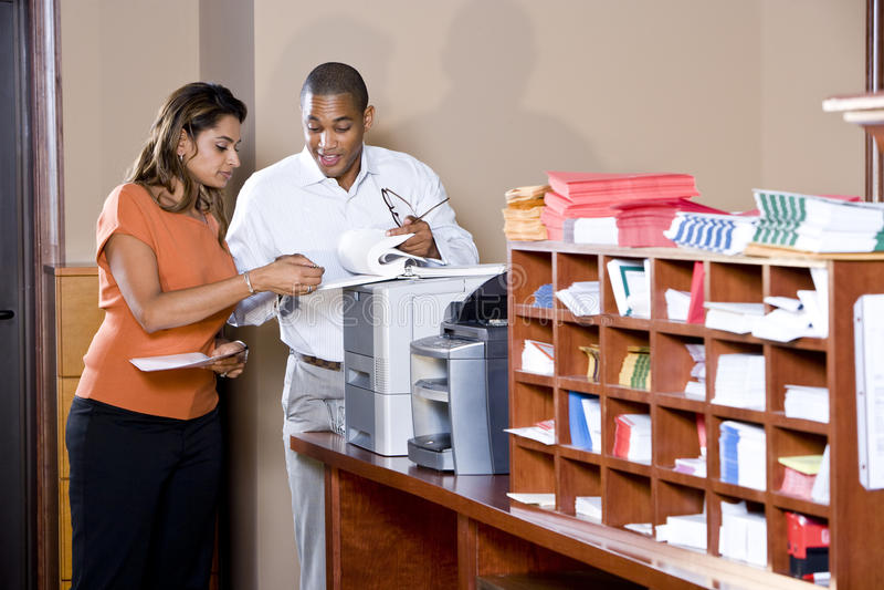 Gemischtrassige Büroangestellte, die an Dokumenten arbeiten lizenzfreie stockfotos