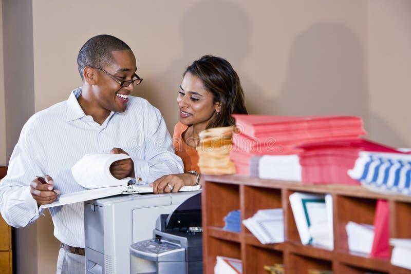 Gemischtrassige Büroangestellte, die an Dokumenten arbeiten stockbild