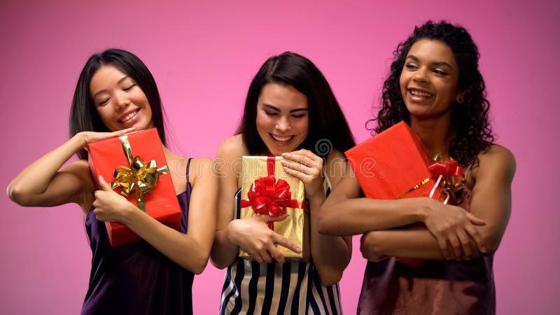 Gemischtrassige Frauen in den Pyjamas, die Geschenkboxen, geheime Sankt-Partei, Feier halten stockfotografie