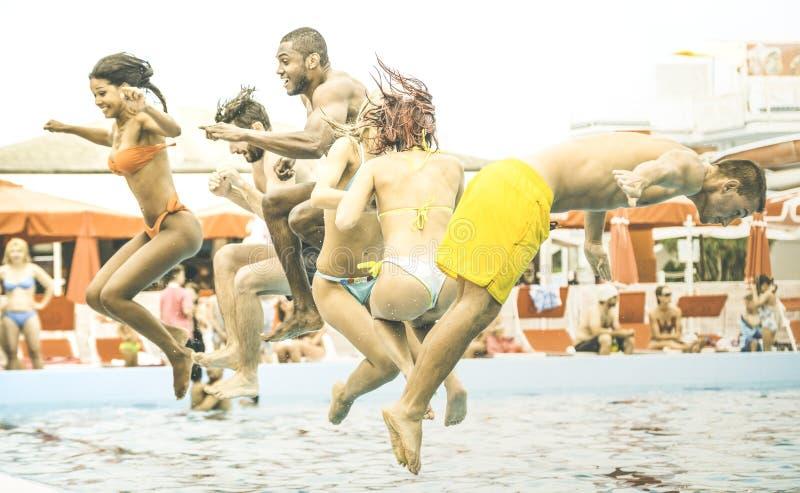 Gemischtrassige Freunde, die den Spaß springt an Schwimmenpool-party aquapark haben lizenzfreies stockfoto