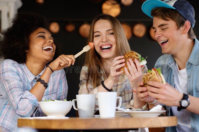 Gemischtrassige Freunde, die in einem Café essen lizenzfreies stockbild