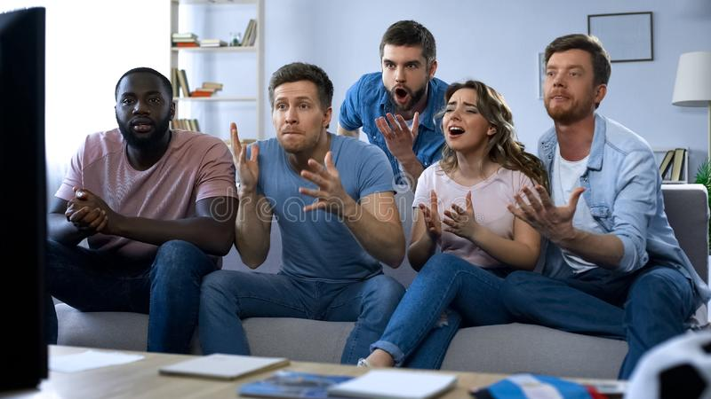 Gemischtrassige Freunde, die zusammen Sportspiel, enttäuscht über Ergebnis aufpassen lizenzfreie stockbilder