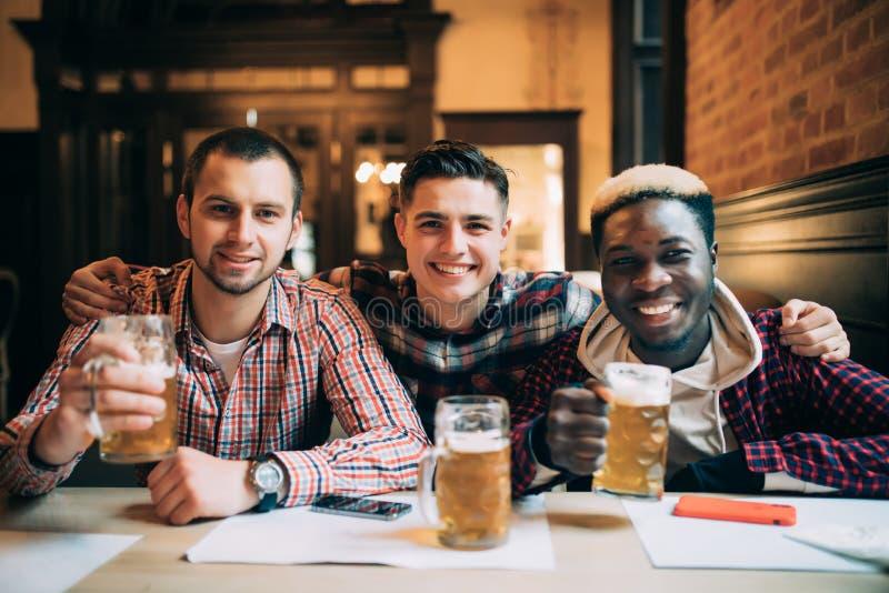 Gemischtrassige Freunde gruppieren das Trinken und das Rösten des Bieres an der Kneipe Freundschaftskonzept mit den jungen Leuten stockbilder
