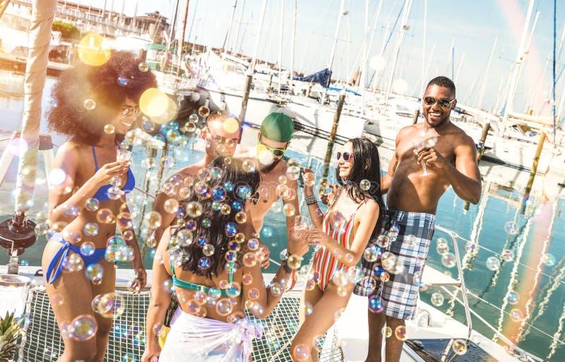Gemischtrassige Freundgruppe, die trinkenden Wein des Spaßes an der Segelbootspartei - Freundschaftskonzept mit jungen ethnisch g lizenzfreie stockfotos