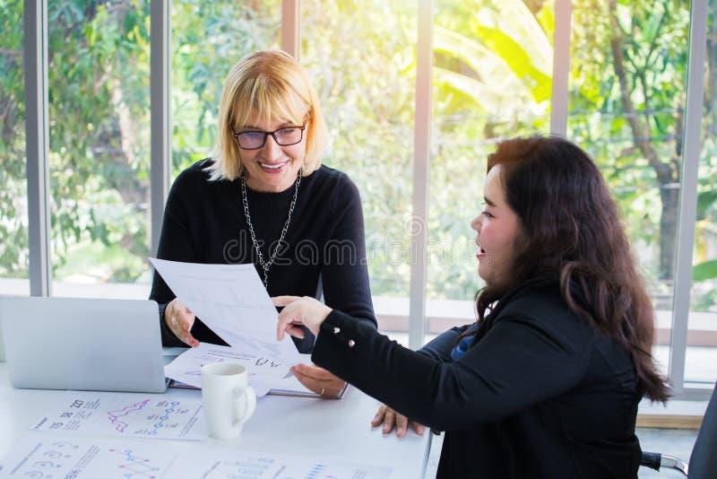 Gemischtrassige Geschäftsfrauen, die Dokument betrachten lizenzfreie stockbilder