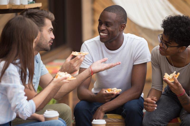Gemischtrassige glückliche Freunde, die über den Witz isst Pizza im Café lachen lizenzfreies stockbild