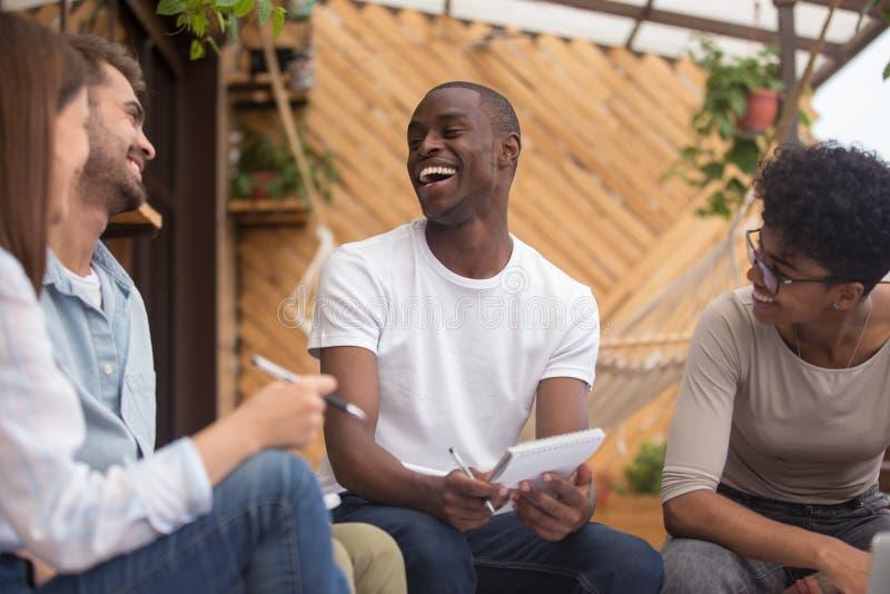 Gemischtrassige glückliche Freunde, die das scherzende Studieren zusammen mit den Notizbüchern im Freien lachen stockbilder