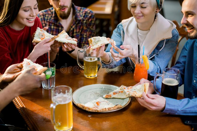 Gemischtrassige glückliche junge Leute, die Pizza in der Pizzeria, nette Freunde lachen essen, die Mahlzeit genießend, die das Sp lizenzfreie stockfotografie