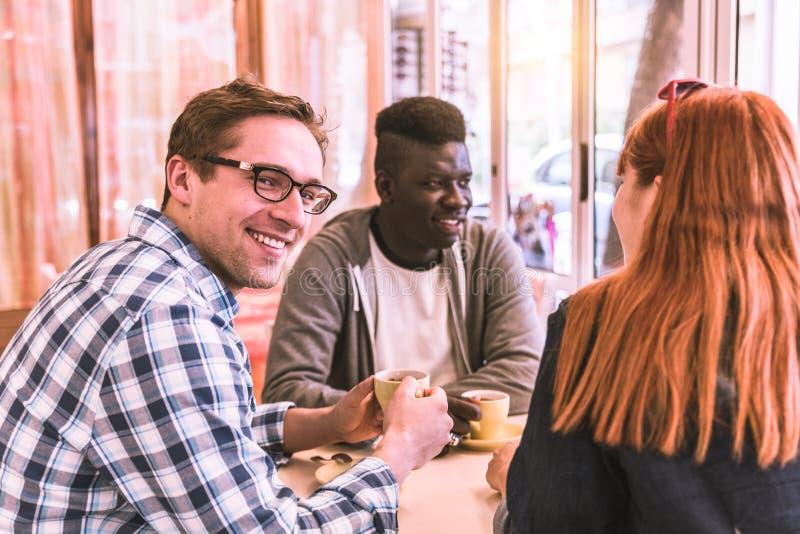 Gemischtrassige Gruppe des Freunds in einem Café lizenzfreie stockfotos