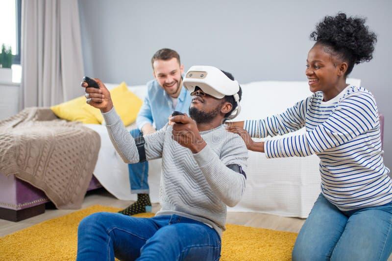 Gemischtrassige Gruppe Freunde, die den Spa? versucht auf Schutzbrillen der virtuellen Realit?t 3D haben stockfotografie
