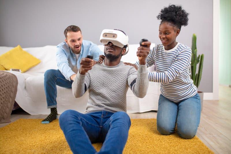 Gemischtrassige Gruppe Freunde, die den Spa? versucht auf Schutzbrillen der virtuellen Realit?t 3D haben stockfoto