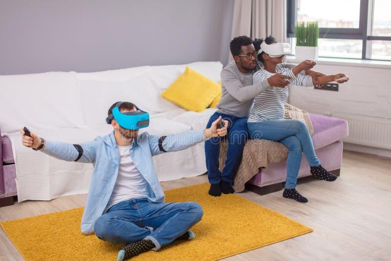 Gemischtrassige Gruppe Freunde, die den Spa? versucht auf Schutzbrillen der virtuellen Realit?t 3D haben stockfotos