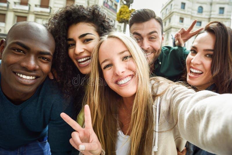 Gemischtrassige Gruppe junge Leute, die selfie nehmen stockfotografie