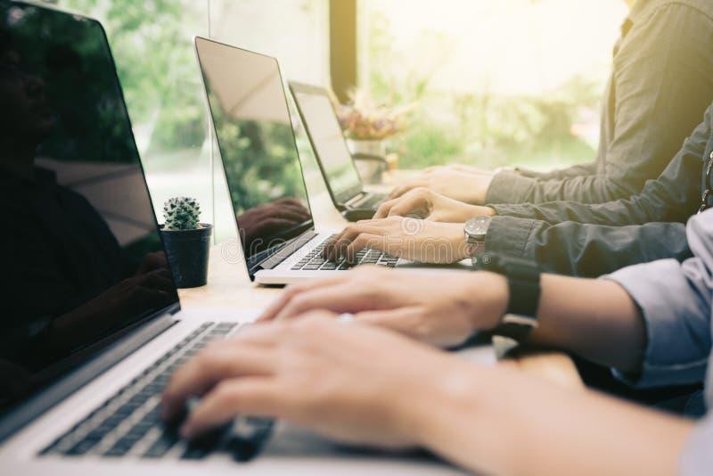 Gemischtrassige Gruppe Studenten, die auf Laptop an coworking spac kodieren stockbild