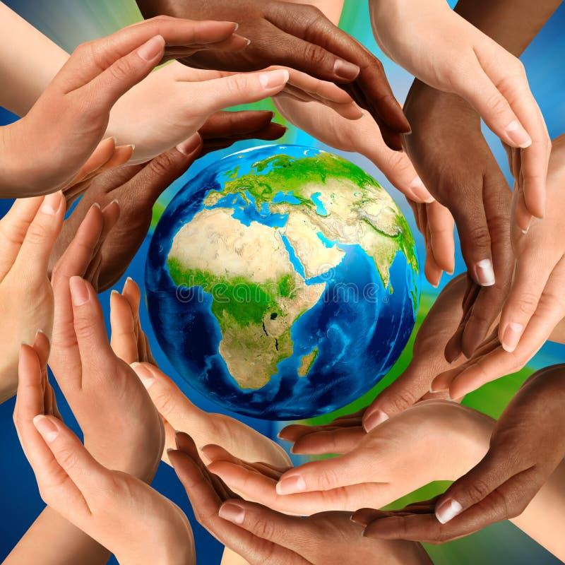 Gemischtrassige Hände um die Erde-Kugel stockfotos