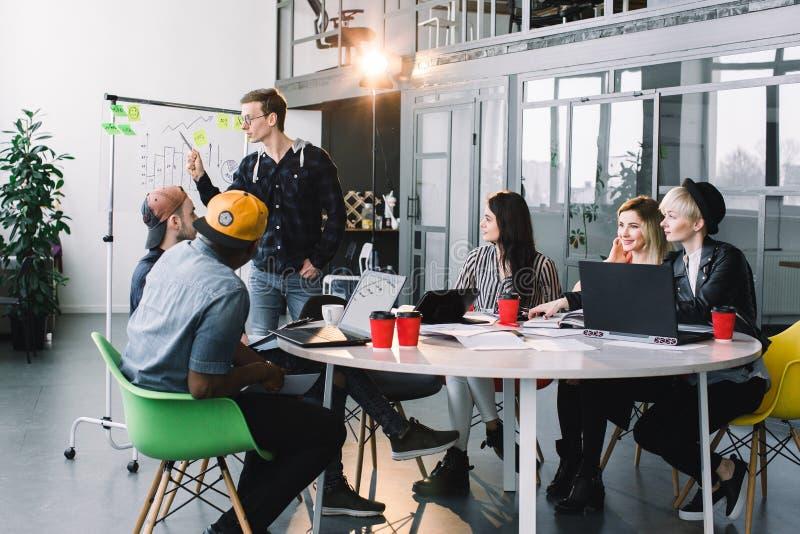 Gemischtrassige junge kreative Leute im modernen Büro arbeiten zusammen mit Laptop, Tablette, intelligentes Telefon, Notizbuch lizenzfreies stockbild