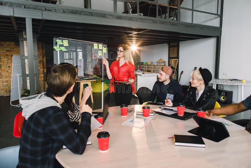 Gemischtrassige junge kreative Leute im modernen B?ro Gruppe junge Gesch?ftsleute arbeiten zusammen mit Laptop stockfoto