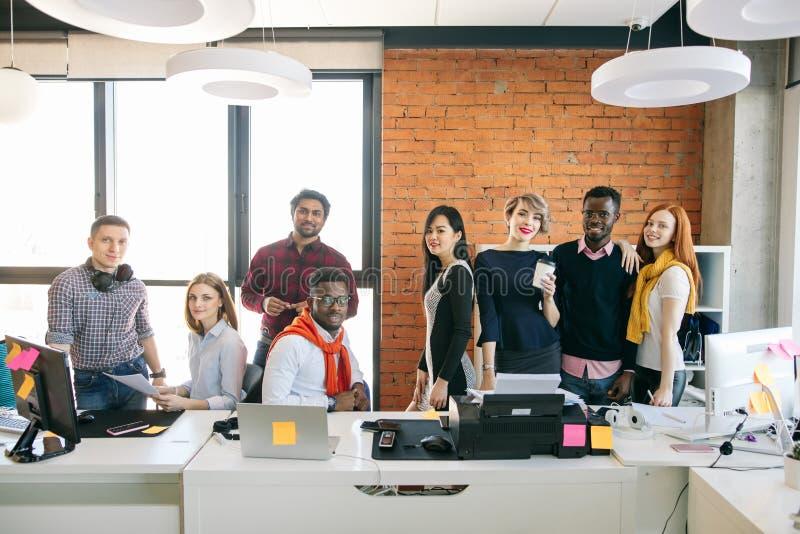 Gemischtrassige kreative Leute im modernen Büro mit Panoramafenster lizenzfreie stockfotos