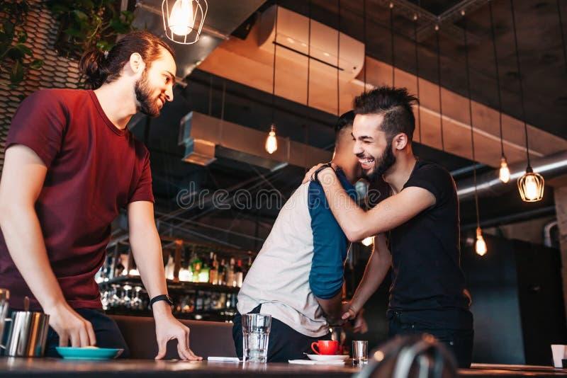Gemischtrassige Männer, die ihren Freund im Aufenthaltsraumcafé treffen Wirkliche Gefühle von den besten Freunden glücklich, sich stockbilder