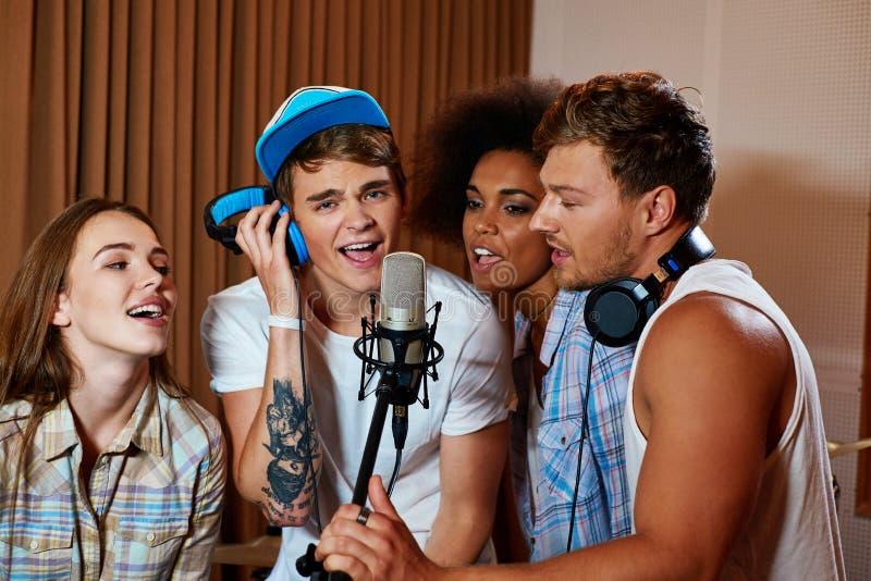 Gemischtrassige Musikband, die in einem Tonstudio durchführt stockfotografie