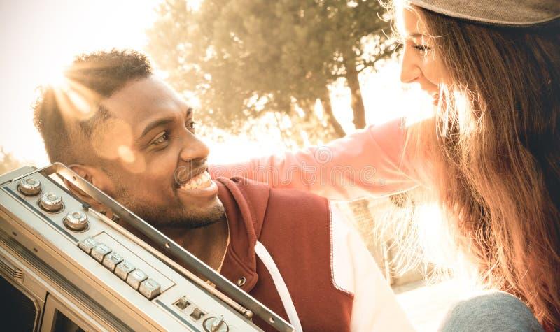Gemischtrassige Paare am Anfang der hörenden Musik der Liebesgeschichte stockfoto