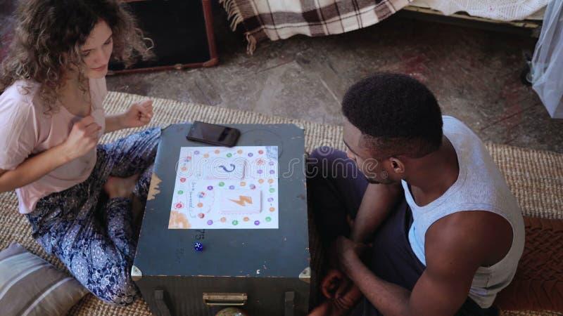 Gemischtrassige Paare, Mann und Frau in den Pyjamas, die das Brettspiel spielen Mädchenwürfe würfeln und tanzend, Verschiebung au stockfotos