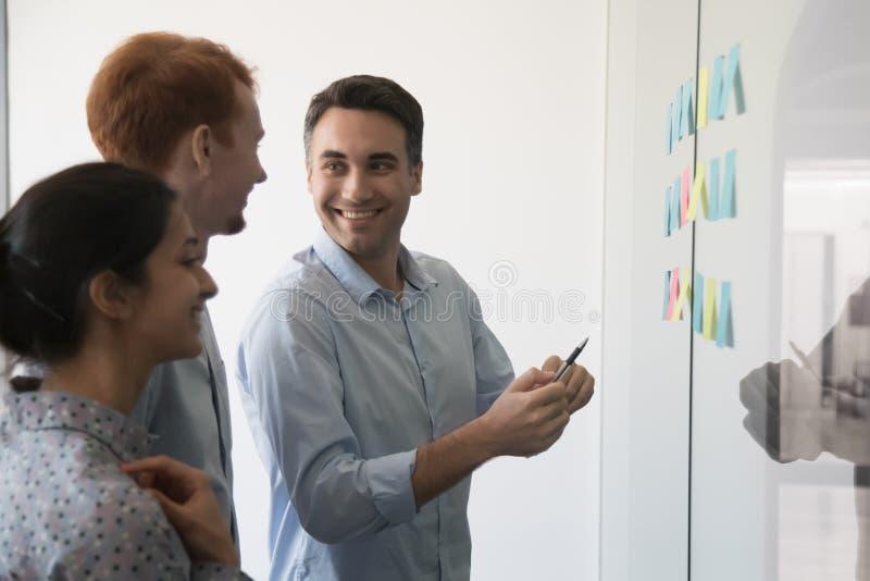 Gemischtrassiges Arbeitsteam besprechen die Idee, die auf Schlaggeräten im Büro dargestellt wird lizenzfreies stockfoto
