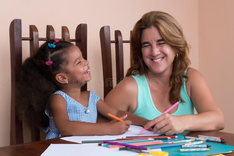 Gemischtrassiges kleines Mädchen und ihre Mutterzeichnung mit Farbbleistiften lizenzfreie stockfotografie