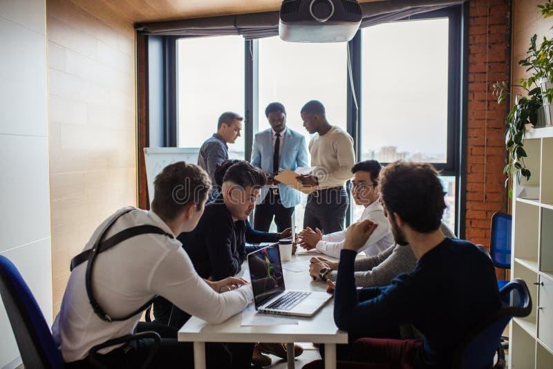 Gemischtrassiges männliches Team, das über neuem Projekt im BüroKonferenzzimmer spricht lizenzfreie stockfotografie