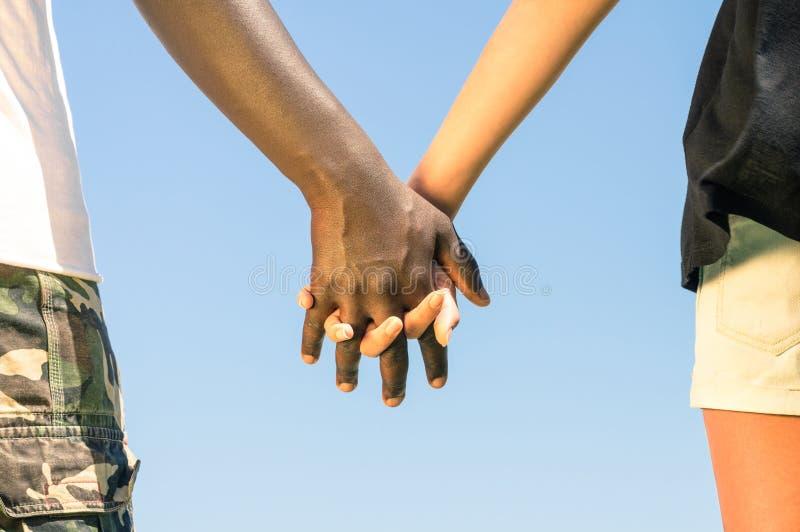 Gemischtrassiges Paarhändchenhalten - Liebe gegen Rassismus lizenzfreie stockbilder