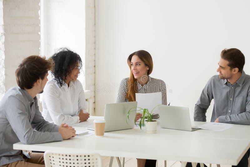 Gemischtrassiges Team, das Arbeitsvertrag in coworking Raum bespricht lizenzfreie stockfotografie