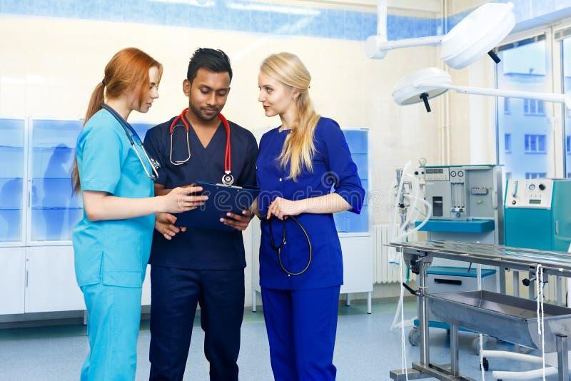 Gemischtrassiges Team von Doktoren, die einen Patienten steht in einem Operationsraum besprechen stockfotografie