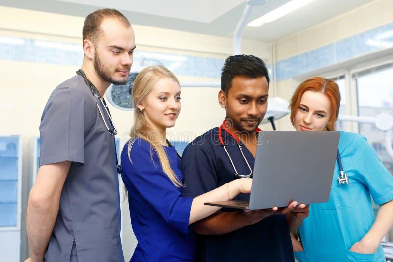 Gemischtrassiges Team von jungen Doktoren, die an Laptop-Computer im Ärztlichen Dienst arbeiten stockbilder
